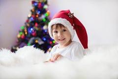 读在圣诞树前面的逗人喜爱的可爱的男孩一本书 库存图片