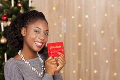 在圣诞树前面的黑人妇女 免版税库存照片