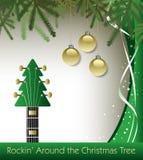在圣诞树吉他背景附近的Rockin' 免版税图库摄影