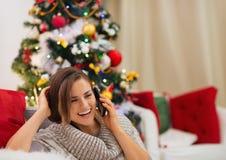 在圣诞树告诉的移动电话附近的愉快的妇女 图库摄影