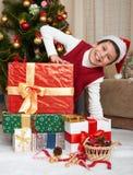 在圣诞树和礼物盒,愉快的假日和冬天庆祝附近的男孩,穿戴在红色 免版税库存照片