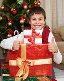 在圣诞树和礼物盒,愉快的假日和冬天庆祝附近的男孩,穿戴在红色 免版税库存图片