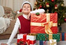 在圣诞树和礼物盒,愉快的假日和冬天庆祝附近的男孩,穿戴在红色 库存图片