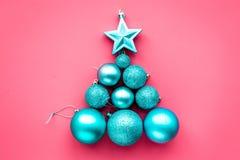 在圣诞树形状的圣诞节玩具  蓝色球和星在桃红色背景顶视图copyspace 库存照片