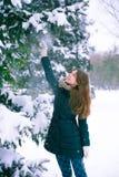 在圣诞树旁边的女孩 免版税库存照片