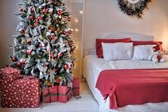 在圣诞树旁边的床 库存图片