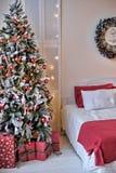 在圣诞树旁边的床 免版税库存图片