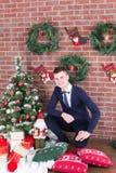 在圣诞树旁边的年轻人 免版税库存照片