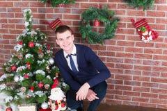 在圣诞树旁边的年轻人 免版税图库摄影