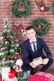 在圣诞树旁边的年轻人 库存照片