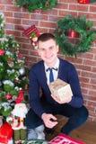 在圣诞树旁边的年轻人 库存图片