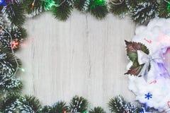在圣诞树框架的白色圣诞节花圈在与诗歌选的木背景分支 Xmas贺卡,看法从 库存照片