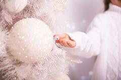 在圣诞树特写镜头的圣诞树玩具 儿童手指人力五个现有量的现有量 库存照片