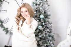 在圣诞树的一条毯子包裹的美丽的少妇 库存照片