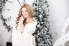 在圣诞树的一条毯子包裹的美丽的少妇 免版税库存照片