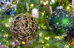在圣诞树的分支的透雕细工金黄球 抽象空白背景圣诞节黑暗的装饰设计模式红色的星形 免版税库存照片
