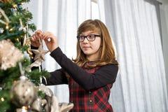 在圣诞树的十几岁的女孩垂悬的装饰品在家 免版税库存图片