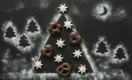 在圣诞树的圣诞节曲奇饼由面粉制成 免版税库存图片