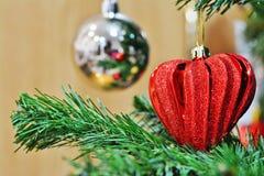 在圣诞树的红色心形的圣诞装饰 库存照片