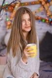 在圣诞树的美丽的少妇饮用的茶 免版税库存照片