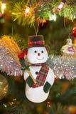 在圣诞树的美丽的滑稽的雪人 免版税库存图片