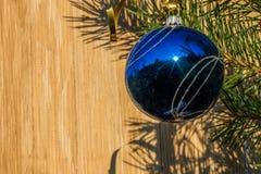 在圣诞树的蓝色装饰球在木背景 库存照片