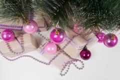 在圣诞树的绿色分支的桃红色球 免版税库存照片