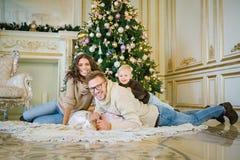 在圣诞树笑附近的愉快的家庭 库存照片