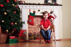 在圣诞树等待前面的愉快的小男孩 免版税图库摄影