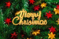 在圣诞树背景的圣诞快乐金黄文本与红色和黄色星 库存照片