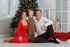 在圣诞树背景的愉快的家庭在家内部与礼物的 免版税库存图片