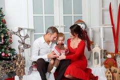 在圣诞树背景的愉快的家庭在家内部与礼物的 库存图片