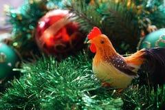 在圣诞树背景的雄鸡  免版税库存图片