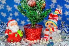在圣诞树附近戏弄圣诞老人和雪人 免版税库存图片