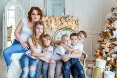 在圣诞树附近照顾和五个孩子 免版税库存照片