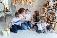 在圣诞树附近照顾和五个孩子 免版税库存图片