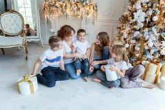 在圣诞树附近照顾和五个孩子 库存照片
