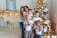 在圣诞树附近照顾和五个孩子 图库摄影