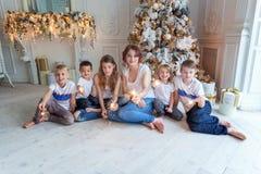 在圣诞树附近照顾和五个孩子 库存图片