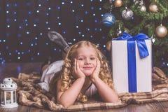 在圣诞树附近的俏丽的儿童女孩 库存照片