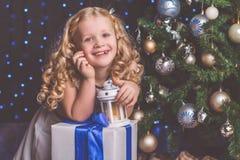 在圣诞树附近的俏丽的儿童女孩 图库摄影