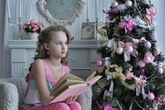 在圣诞树附近的十几岁的女孩 库存图片