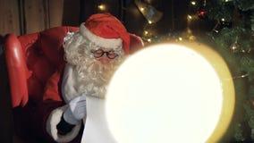在圣诞树附近的圣诞老人读新年礼品单的 影视素材