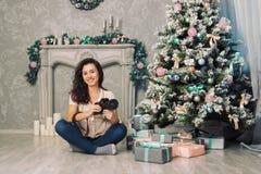 在圣诞树附近的女孩摄影师 免版税库存图片