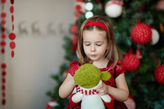 在圣诞树附近的女孩 免版税库存照片