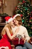 在圣诞树附近的好的爱夫妇 妇女和人celebrat 免版税库存照片