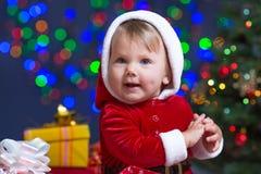 在圣诞树附近的小圣诞老人与礼品 免版税库存照片
