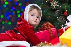 在圣诞树附近的小圣诞老人与礼品 免版税库存图片