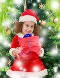 在圣诞树附近的小女孩与一件礼物在它的手上 免版税库存图片
