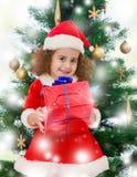 在圣诞树附近的小女孩与一件礼物在它的手上 免版税库存照片
